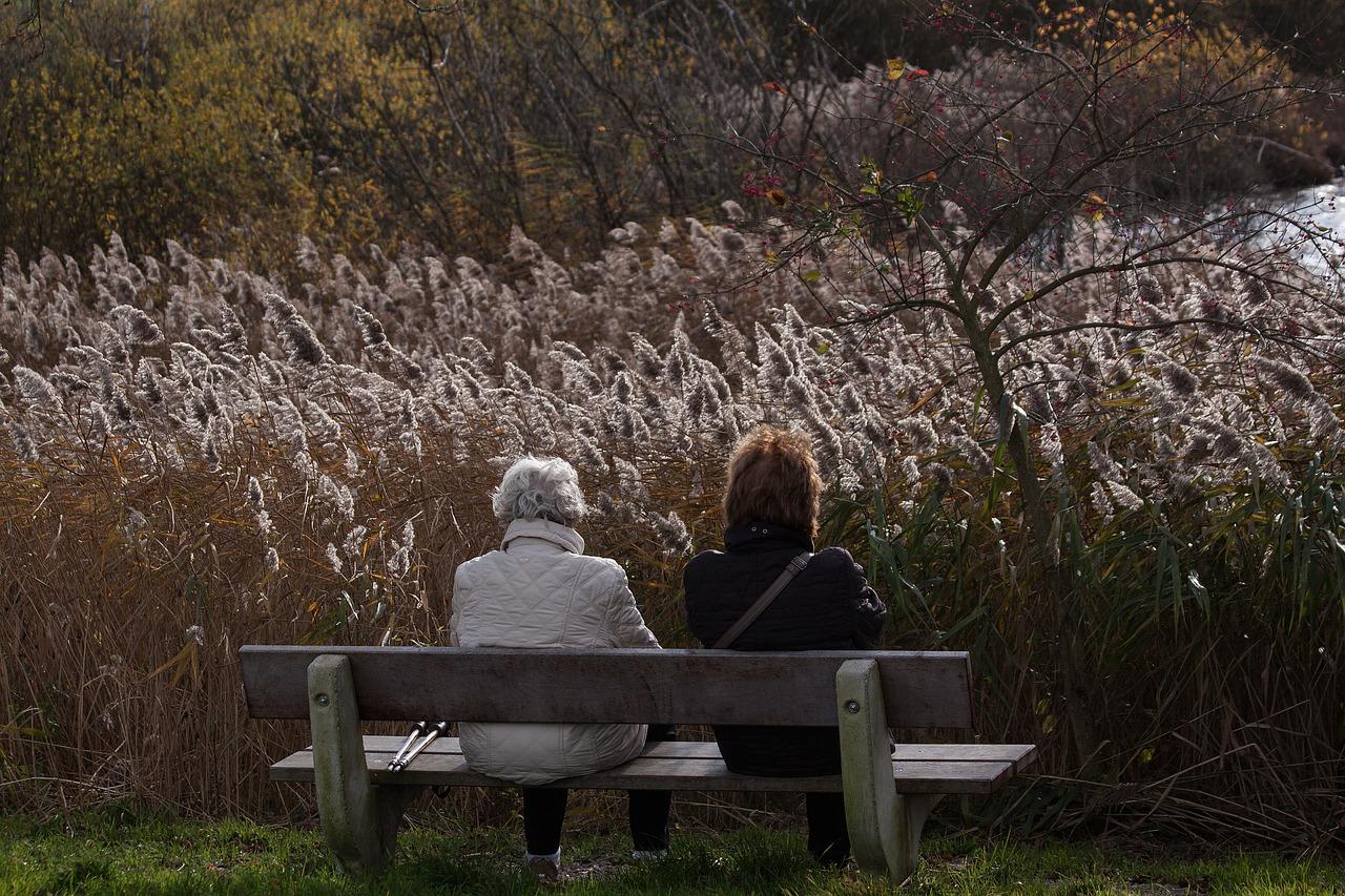 Ženy so šedinami sedia na lavičke
